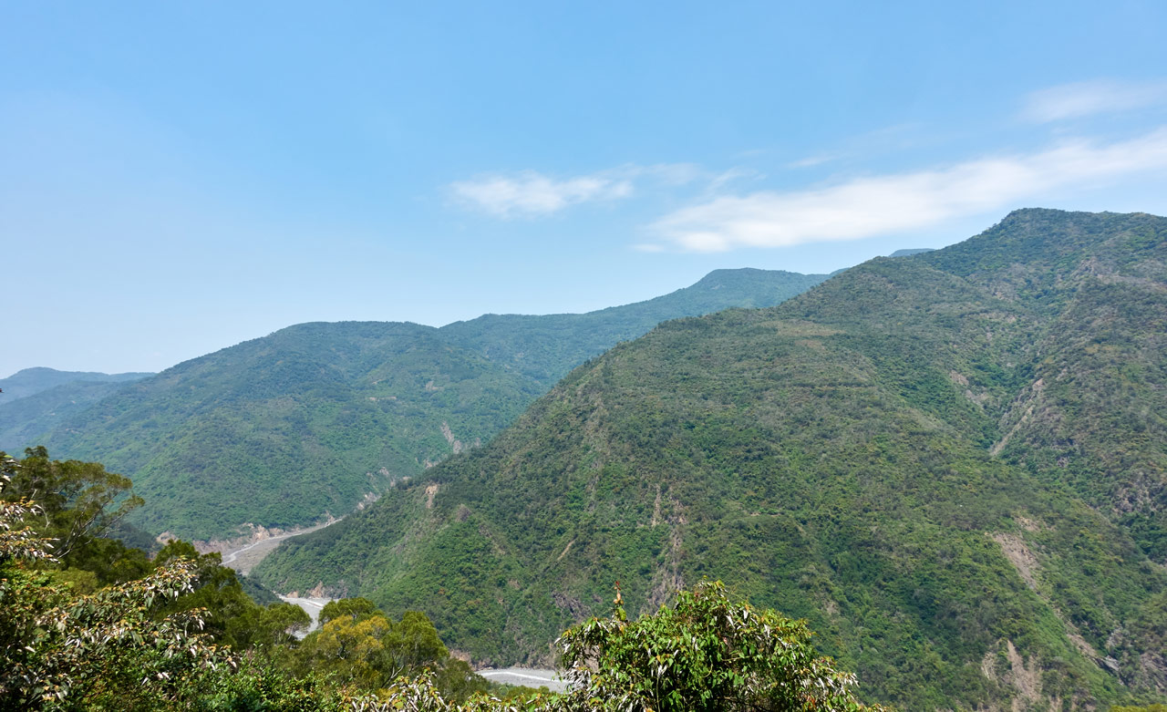 Mountain landscape - riverbed below - blue sky and some clouds