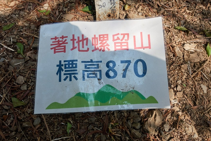 Laminated paper sign attached to tree with Chinese writing on it