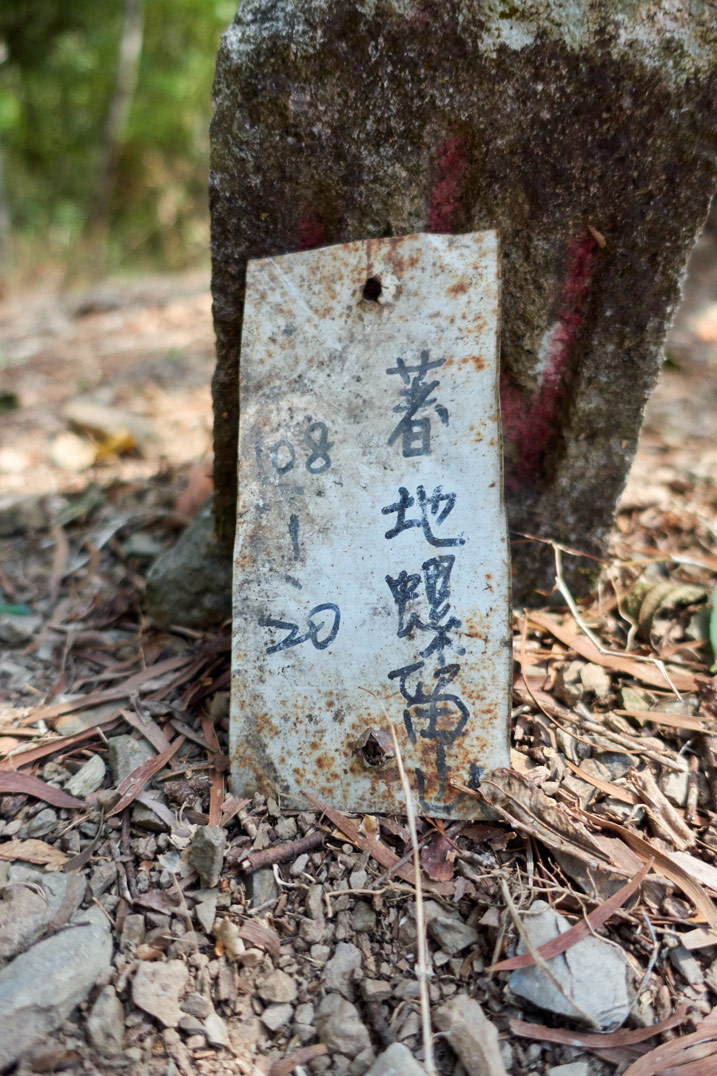 Small white metal sign with chinese writing on it - next to triangulation stone