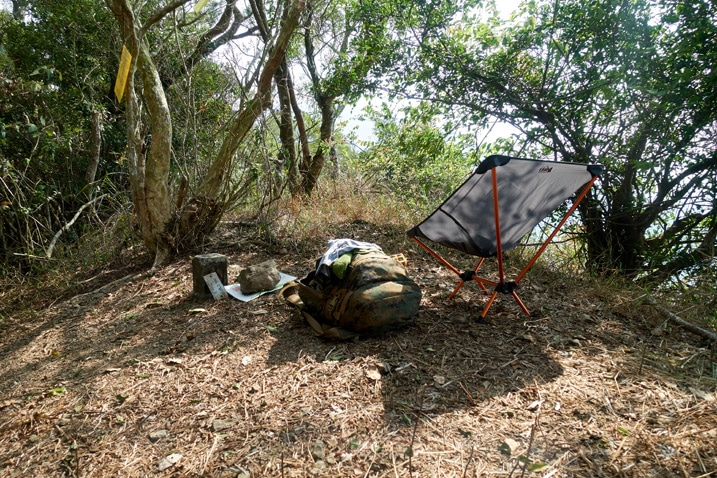 Camp chair, backpack and misc items on ground next to triangulation stone - trees all around
