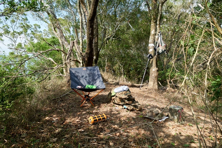 Camp chair, backpack and misc items on ground on mountain peak - trees all around