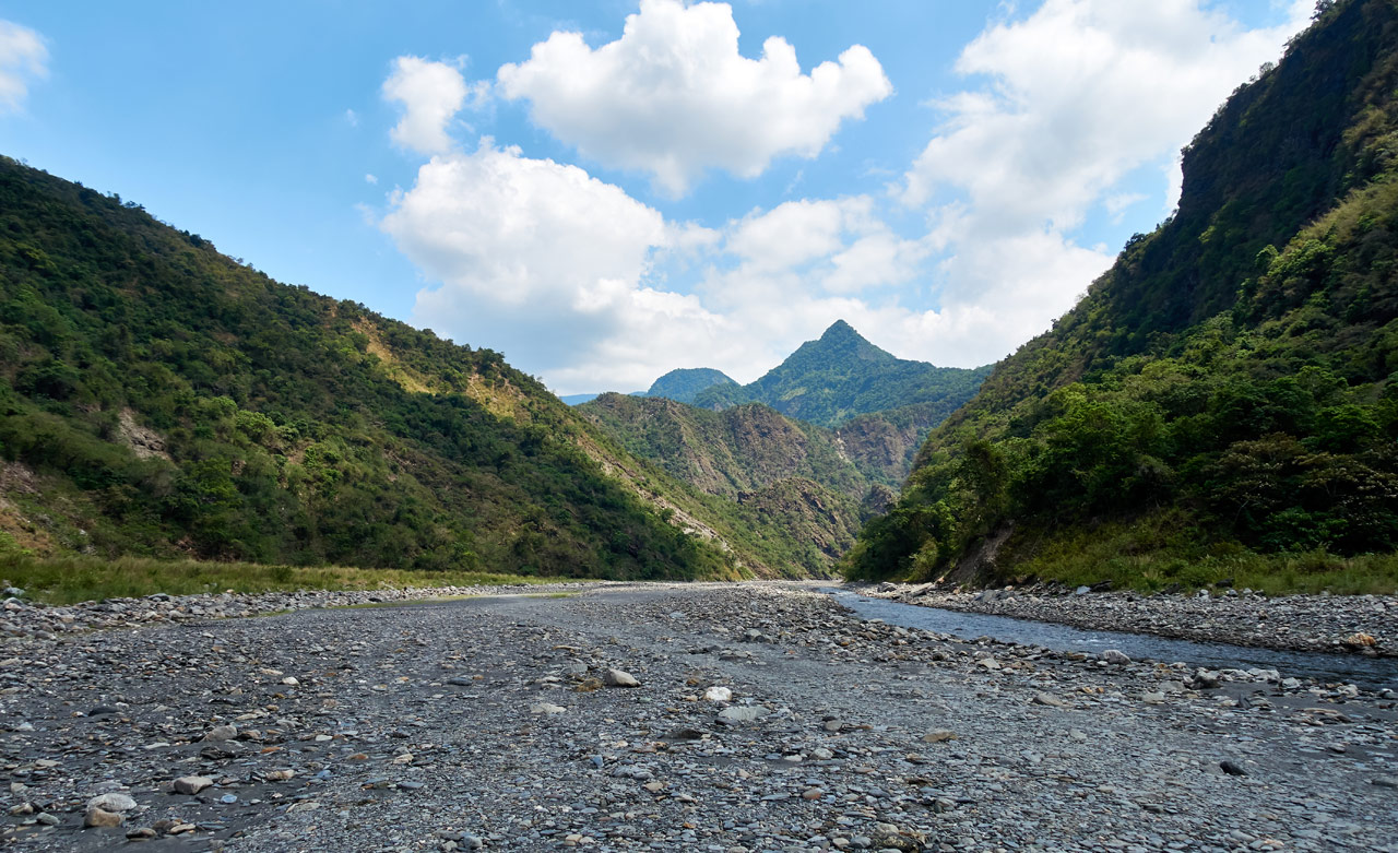 Wide rocky riverbed with mountains in the distance - blue sky and white puffy clouds