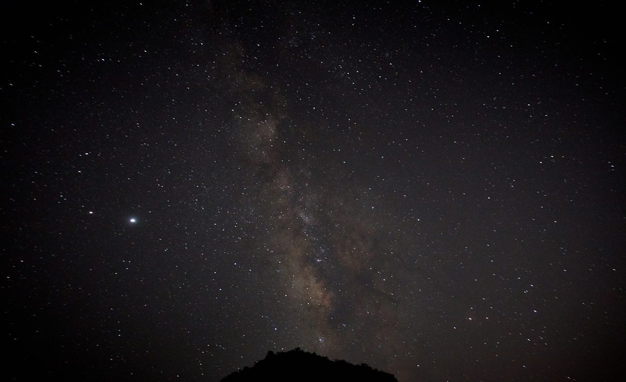 Night picture - most of the milky way with the tip of a mountain peak at the bottom