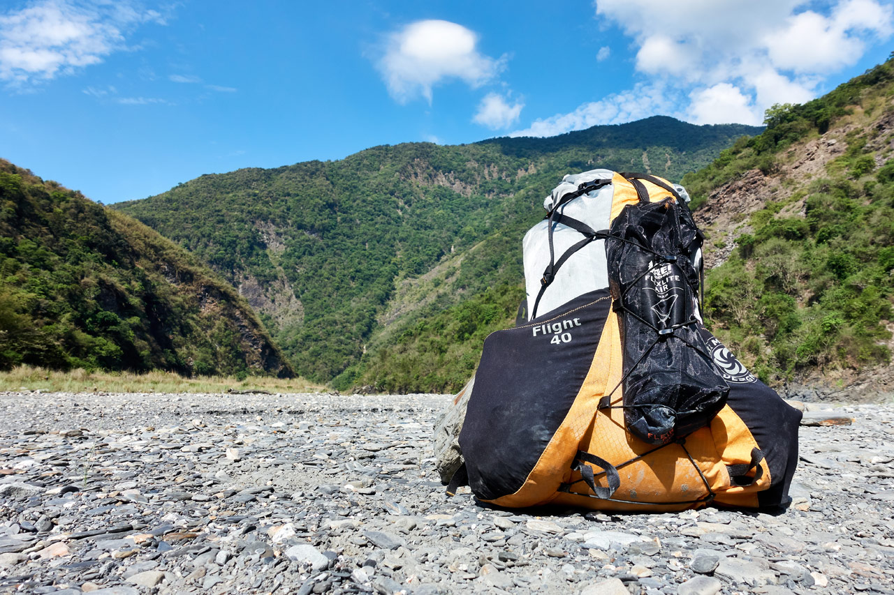 SMD Flight 40 FKT backpack sitting on rocky riverbed - mountains and blue sky in distance