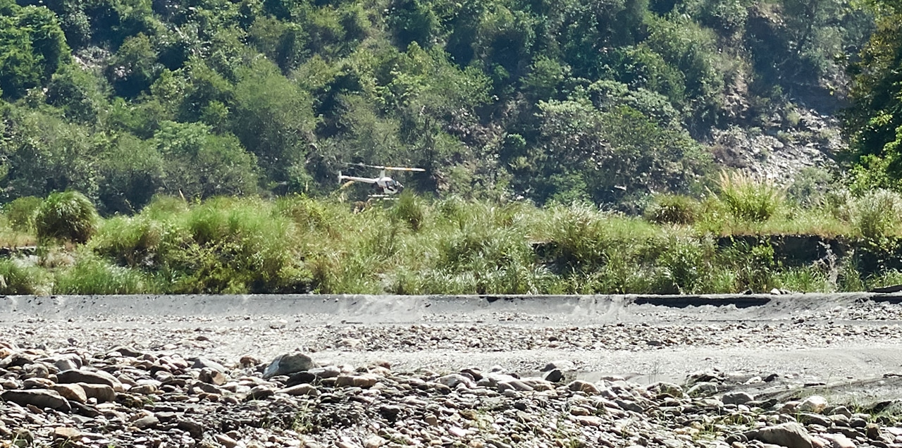 Small helicopter flying close to rocky riverbed - green trees in background