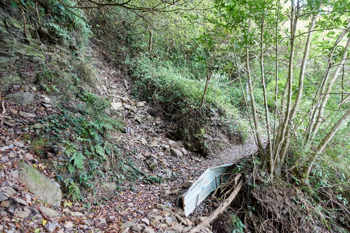rocky dirt trail - small landslide patched up with corrugated metal