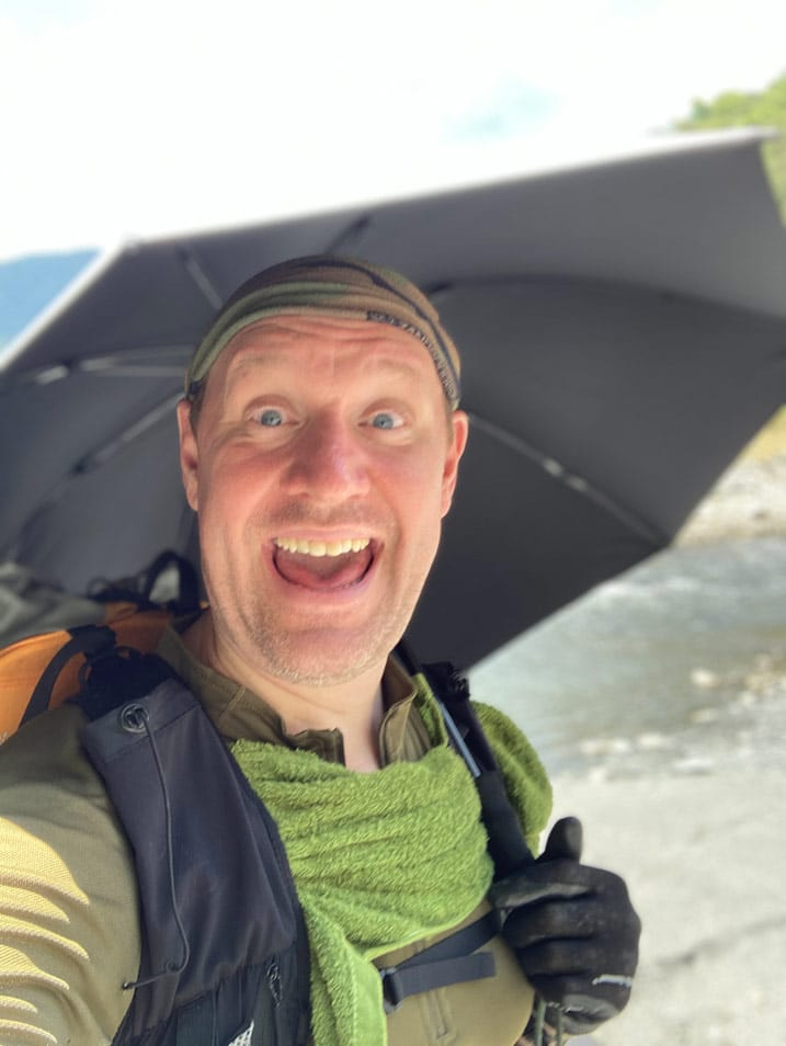Smiling man under SMD umbrella taking selfie