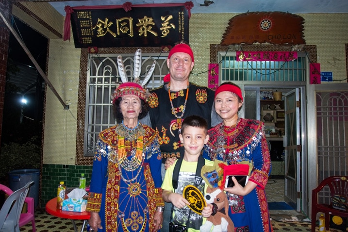 four people in Paiwan traditional clothing standing in front of house for picture