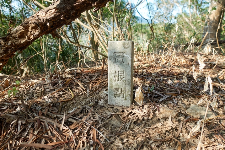 White stone marker in the ground with three Chinese characters written on it