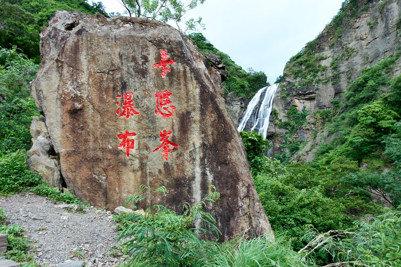 Rock with Chinese words painted in red - waterfall beyond
