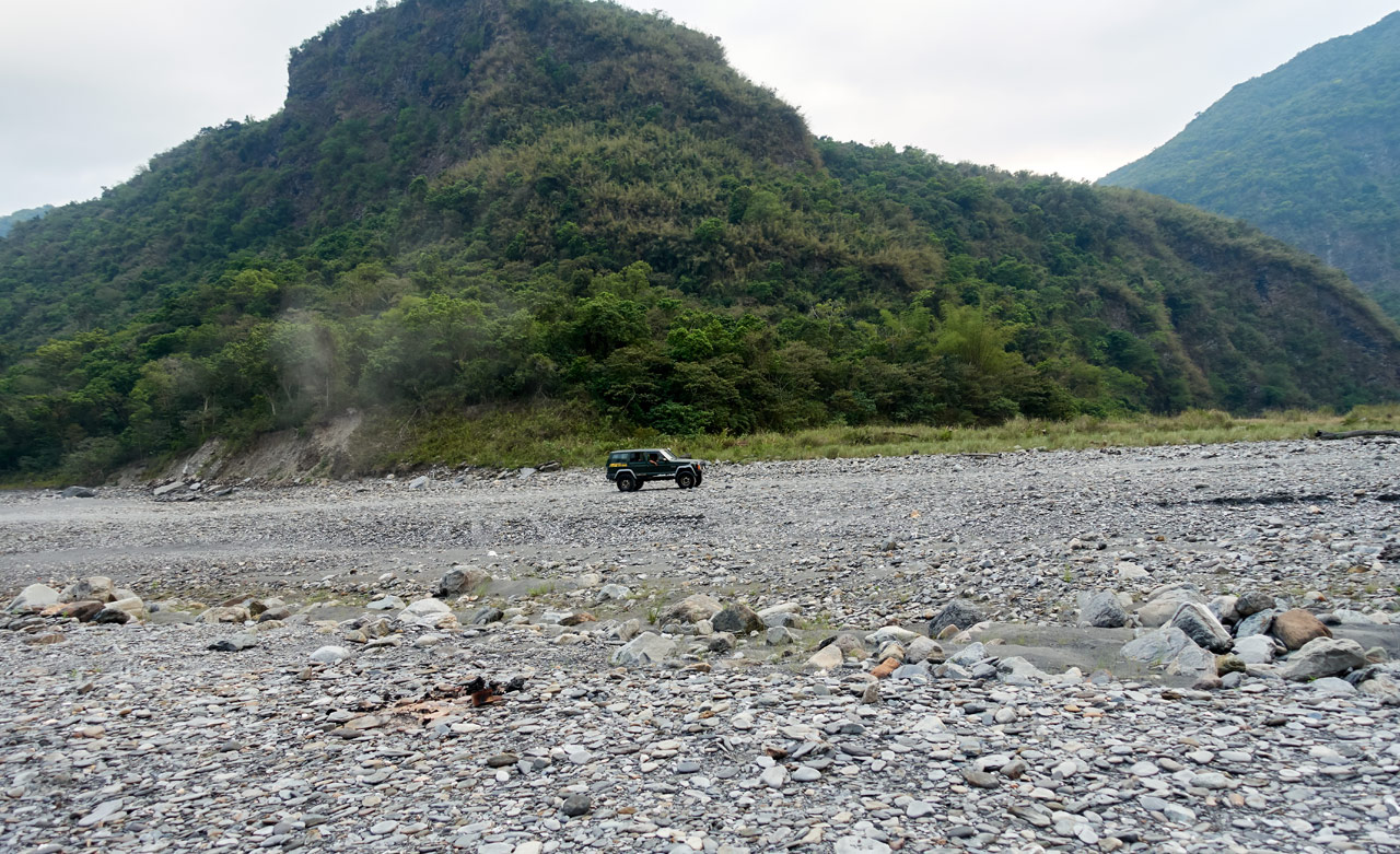 4x4 driving on rocky riverbed - mountain in background