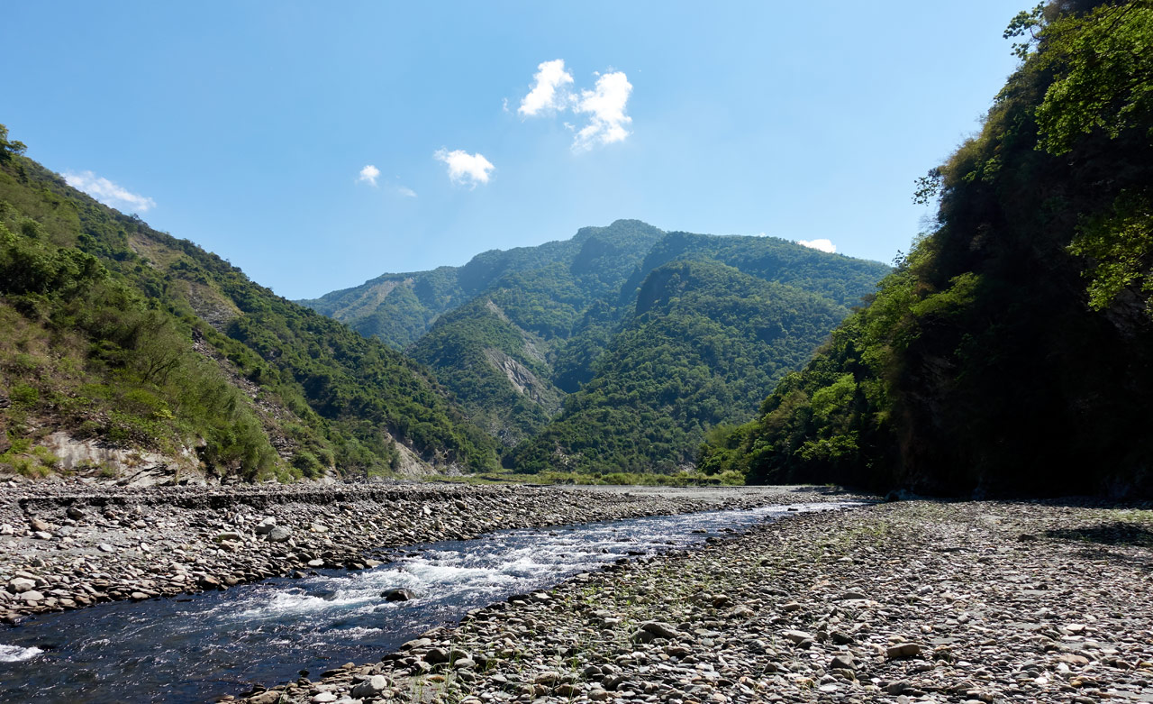 Rocky riverbed and mountains in the distance - Blue sky