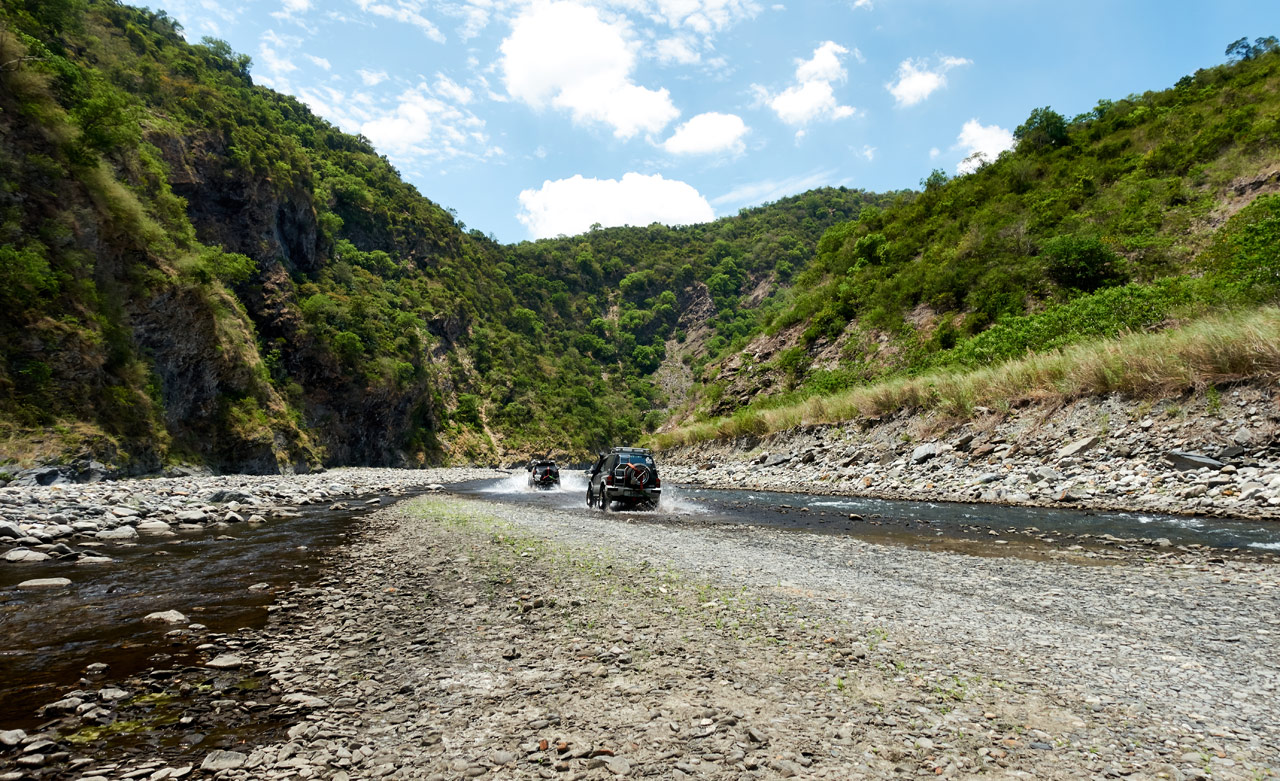 Two SUV's driving on rocky riverbed - mountains in distance - blue sky with white clouds