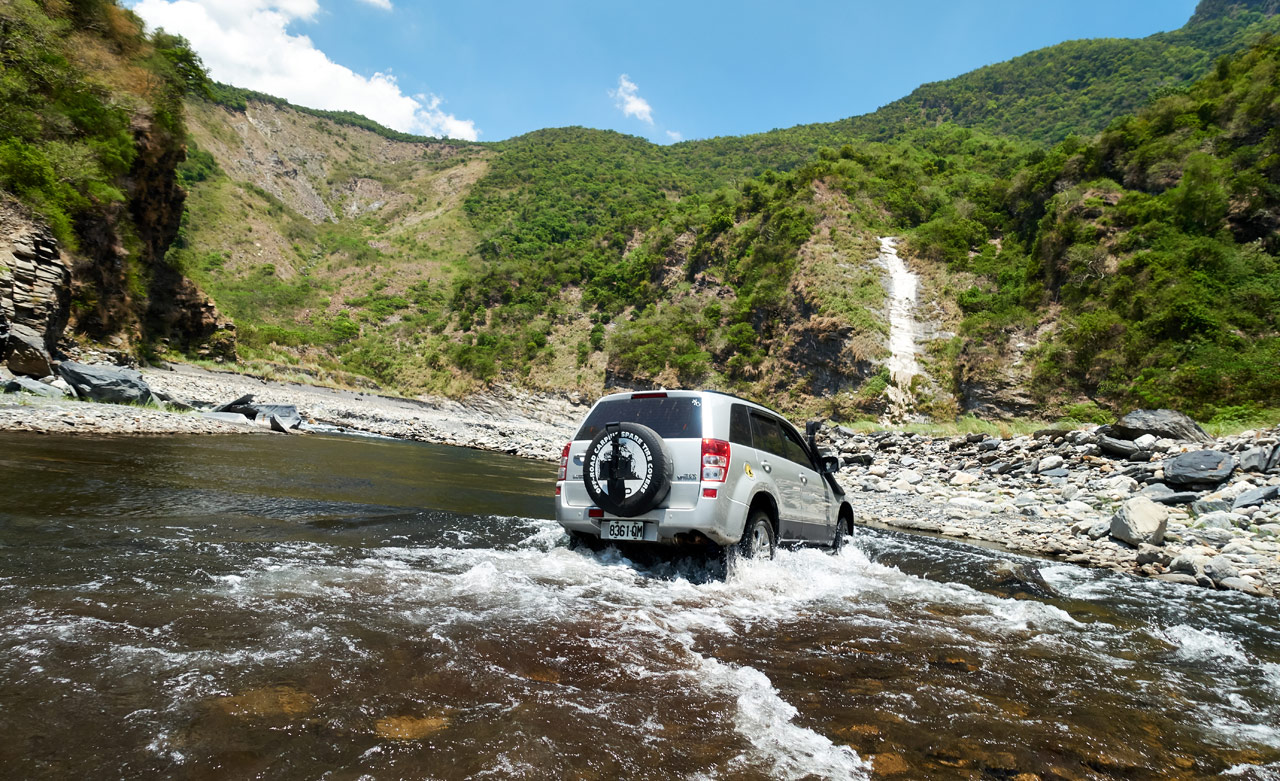 SUV crossing rocky riverbed - mountains in background - blue sky
