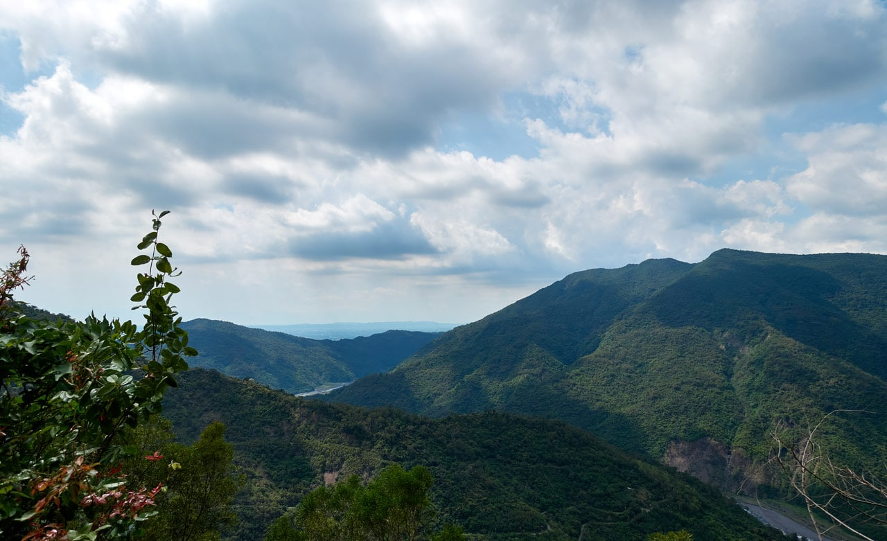 Mountain landscape with river below - mostly cloudy with some blue sky