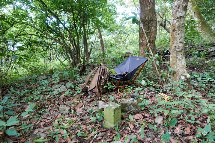 Camp chair and backpack set up near a triangulation stone - trees in background