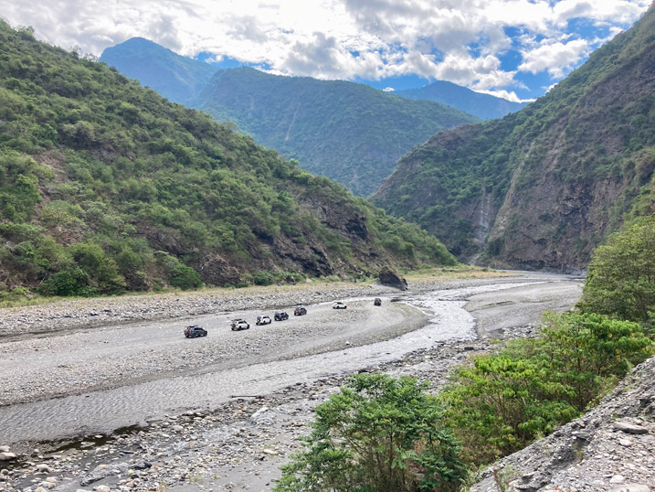 Convoy of 4x4 vehicles on wide riverbed - mountains in distance
