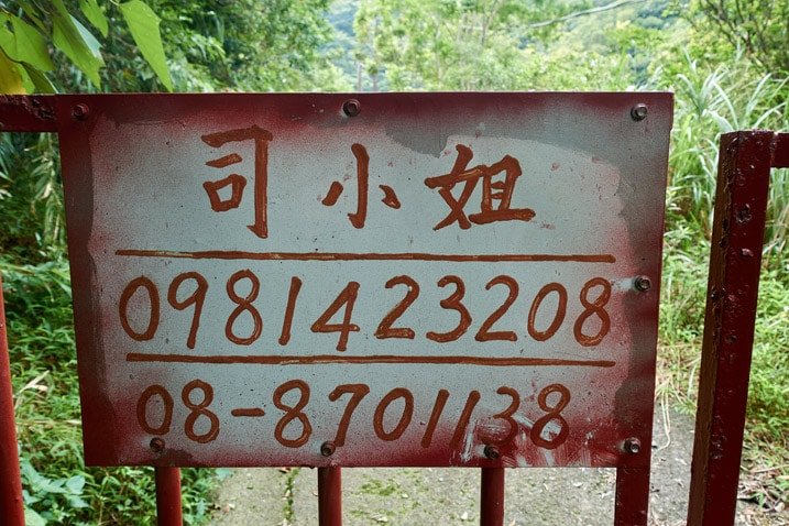 Sign on gate with name and phone number - written in Chinese