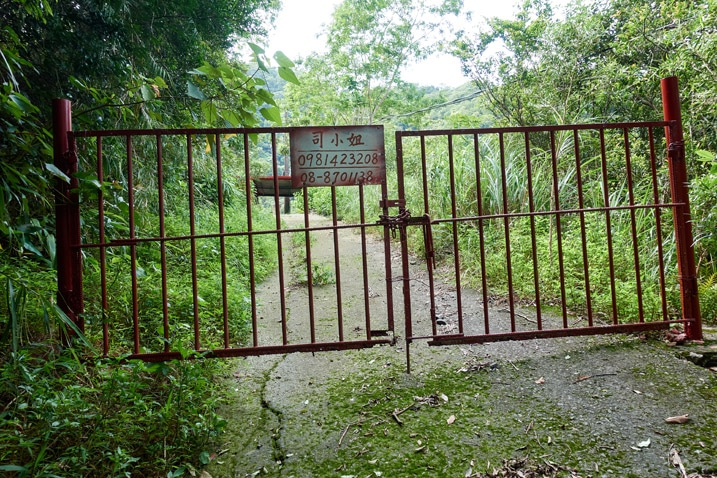 Locked gate blocking road - sign on gate with name and phone number