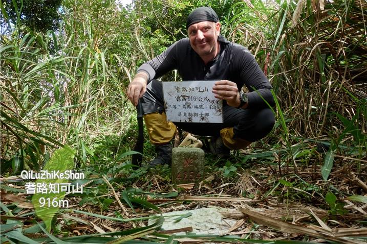 Man standing behind QiLuZhiKeShan - 耆路知可山 triangulation stone holding sign and machete - tall grass around him