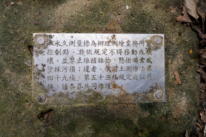Little plaque with Chinese words written on it at base of triangulation stone