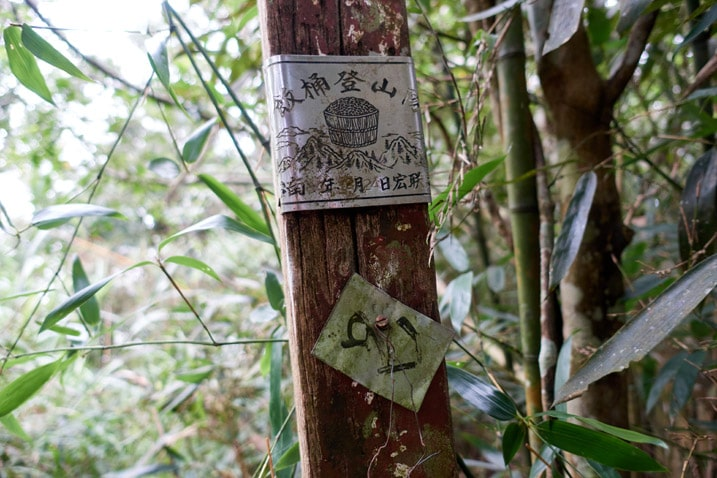 Little signs attached to wooden sign post