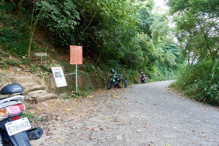 Mountain road with motorcycles parked - signs on left