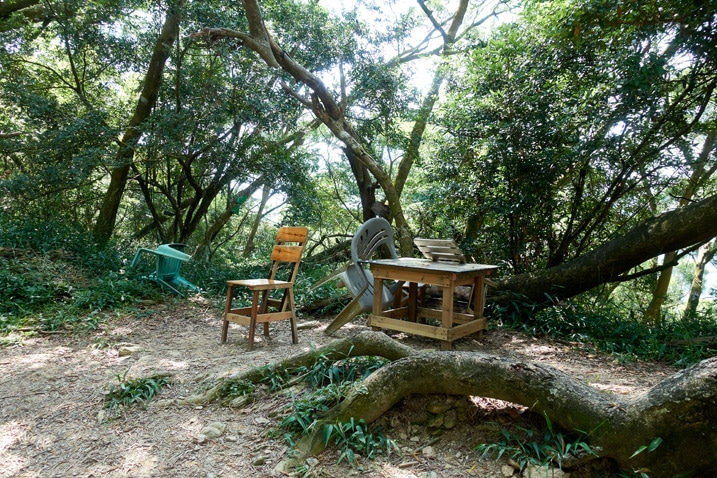 Wooden desk and two wooden chairs next to trail - trees behind them