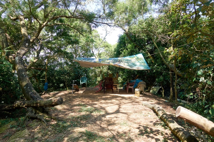 Cleared dirt area in mountains with table, chairs and tarp