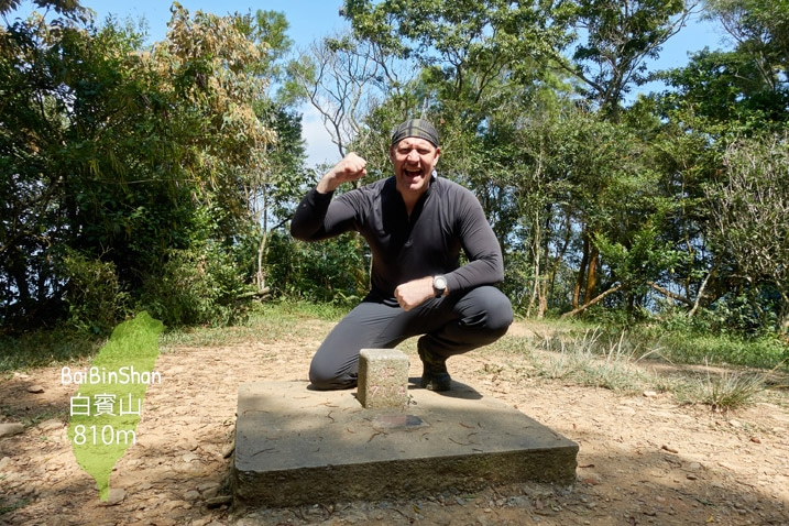 Man kneeling triumphantly behind triangulation stone