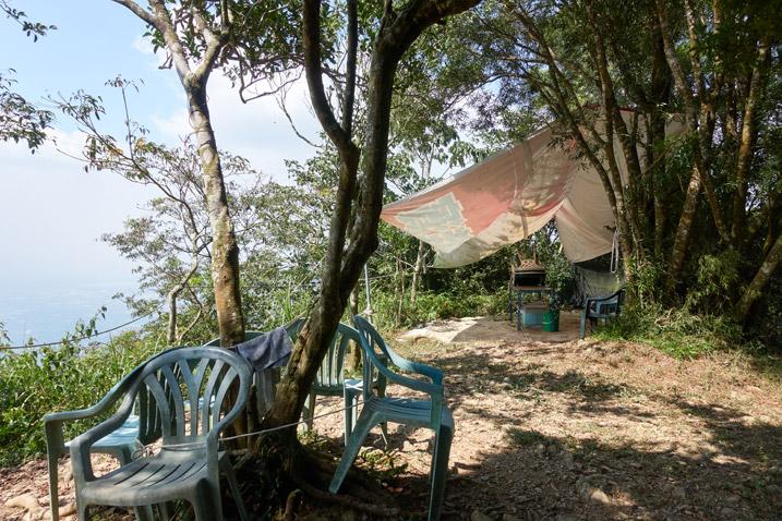 Tarp, table and chairs near tree on mountain ridge