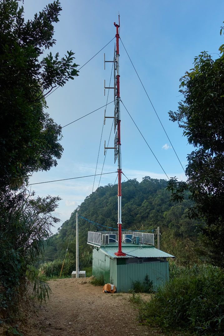 Radio antenna coming out of a small building - mountain in distance