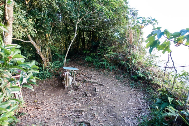 Open dirt area on mountain ridge with chairs and table - trees all around