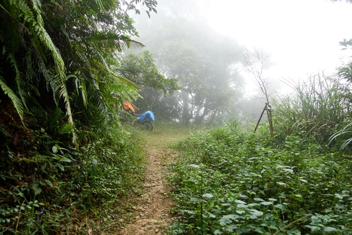 Dirt path in mountain jungle - foggy - motorcycle parked in distance