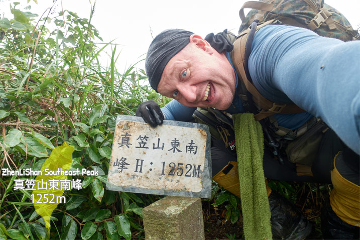 Man holding sign with Chinese characters - triangulation stone - hiker