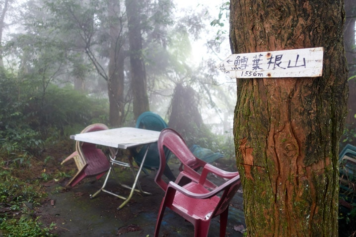 Table and plastic chairs on mountain ridge - tree with sign pointing to the left