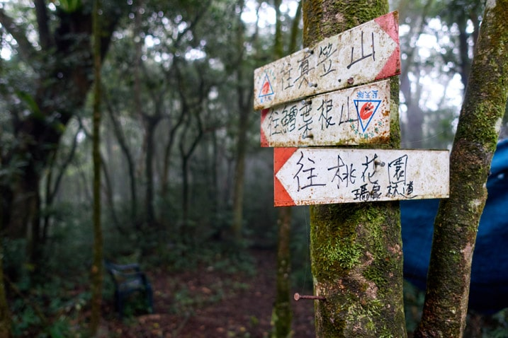 Three signs in Chinese pointing the directions to different mountains - trees in background