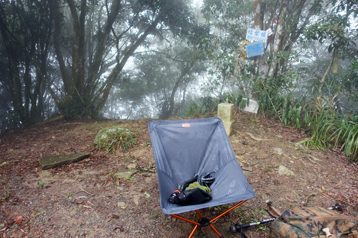 Camp chair on mountain peak - open area - trees in background - foggy