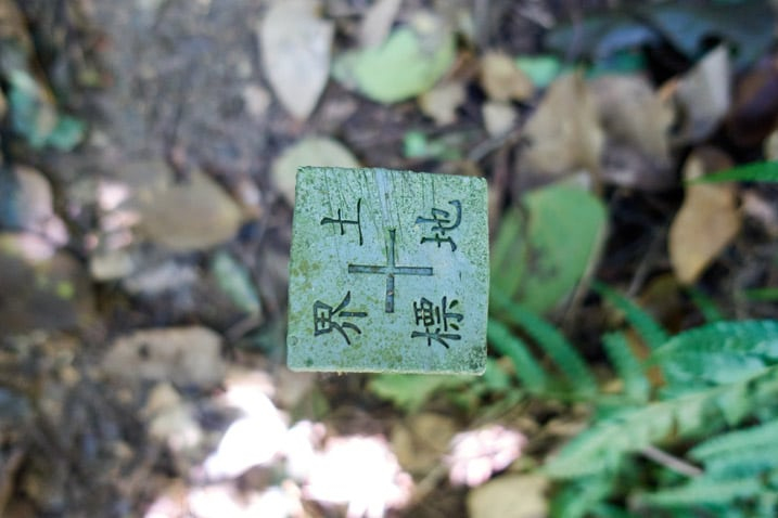 Closeup of top of plastic marker next to trail - square shape - Chinese writing on it