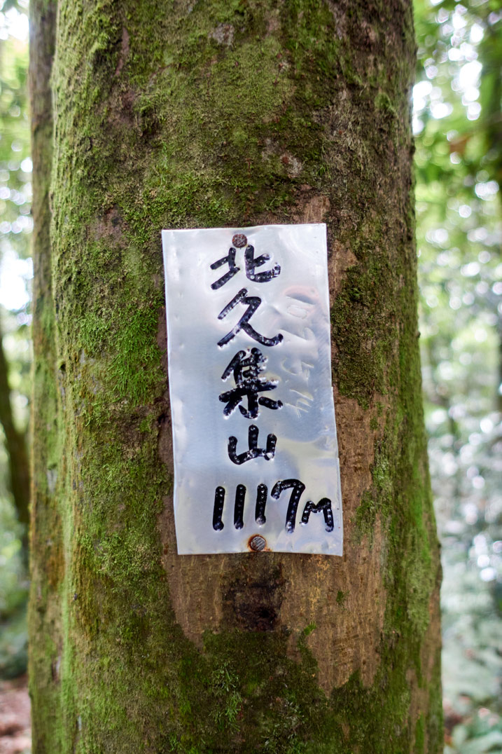 Small metal sign nailed to tree with 北久集山 1117m written on it