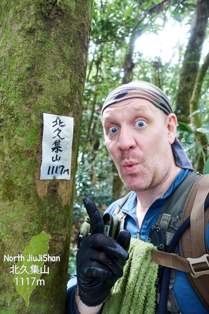 Man posing next to sign on tree with name of mountain in Chinese