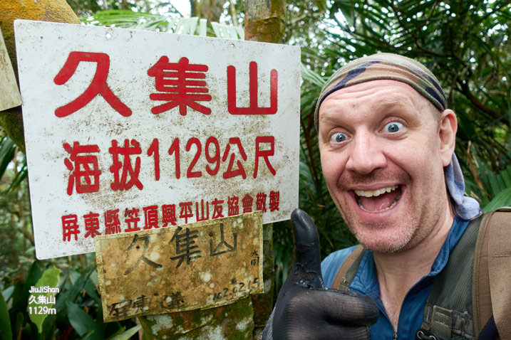 Jiujishan - 久集山 Peak - Man next to sign with happy look on his face