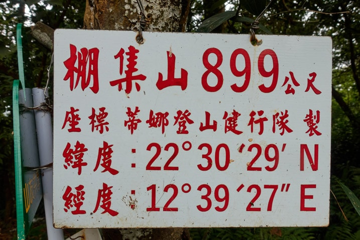 Closeup of white sign with red chinese words attached to a tree