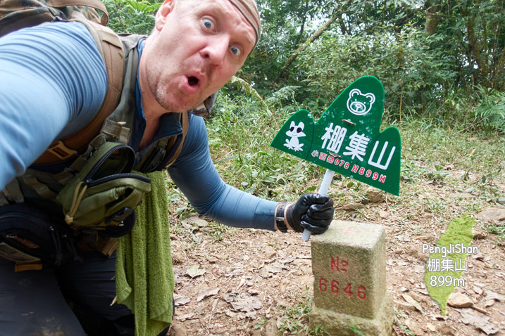 Man holding green sign near PengJiShan - 棚集山 triangulation stone