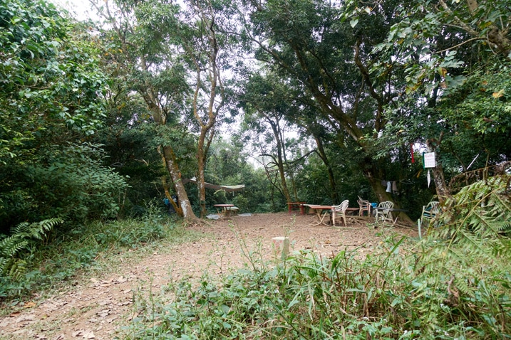 Open dirt area - chairs and tables all around - many trees in background - PengJiShan - 棚集山