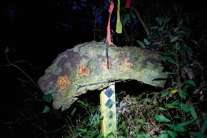 Wooden sign in the dark lit up by headlamp - Chinese words written on sign