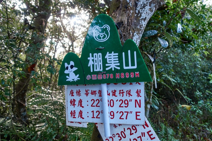 Green sign with handle for PengJiShan 棚集山 - attached to tree