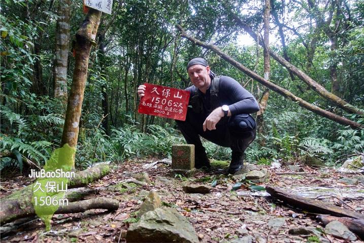 Man crouching behind triangulation stone of JiuBaoShan 久保山 holding a sign
