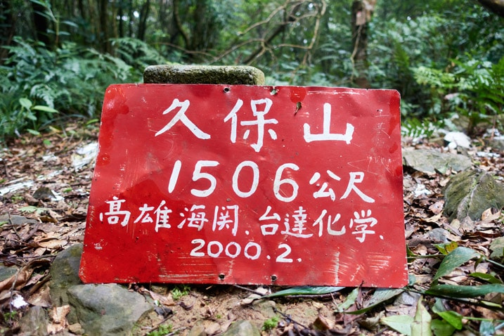Closeup of red metal sign with with Chinese characters - JiuBaoShan 久保山