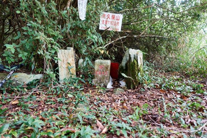 Triangulation stone and some rocks and a sign on a tree for NanJiuBaoShan 南久保山